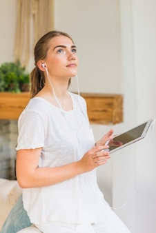 Young woman with earphone holding digital tablet looking away