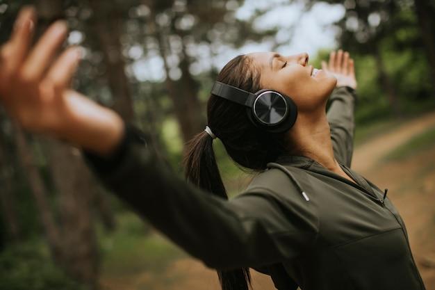 Молодая женщина с наушниками, готовя ее руки в лесу, потому что она любит тренироваться на улице
