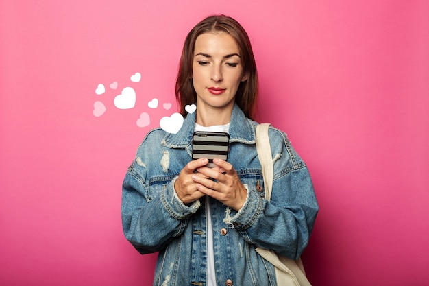 핑크 벽에 초점을 맞춘 전화보고 에코 가방 젊은 여자.