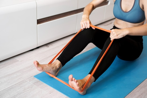 Young woman with elastic band. she trains her legs at home