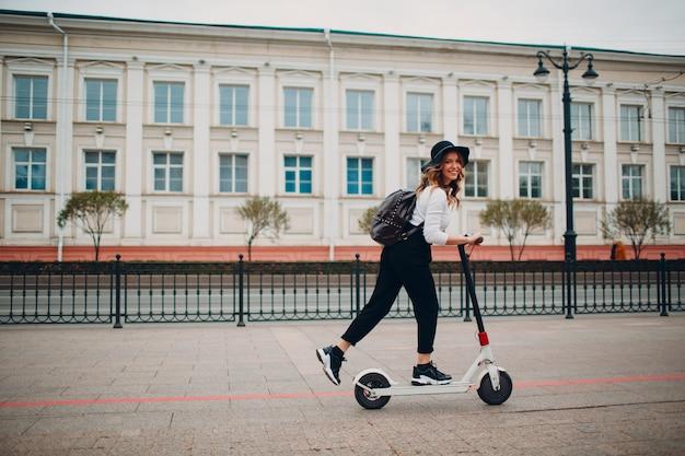 街で電動スクーターを持つ若い女性