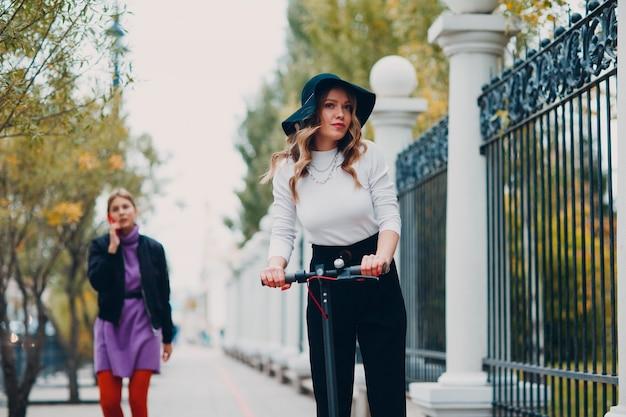 Молодая женщина с электросамокатом в городе.