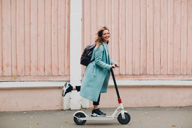 街で青いコートを着た電動スクーターを持つ若い女性