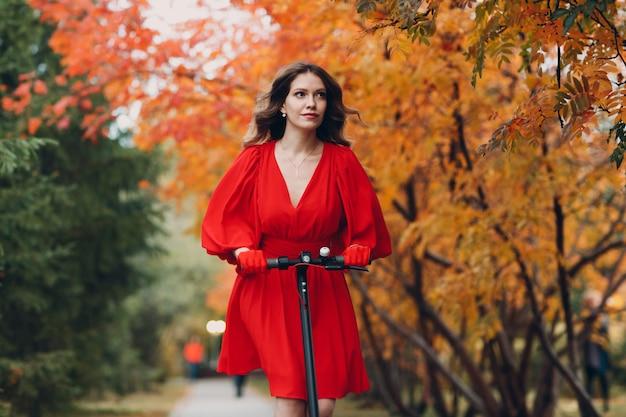 秋の都市公園で赤いドレスと手袋の電動スクーターを持つ若い女性