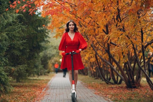 Молодая женщина с электрическим самокатом в красном платье в осеннем городском парке.