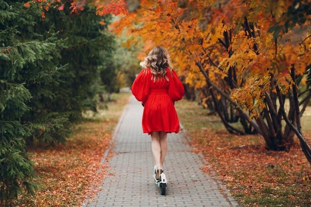 秋の都市公園で赤いドレスを着た電動スクーターを持つ若い女性