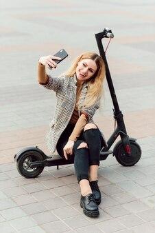 市内の電動スクーターを持つ若い女性