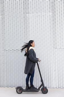 Giovane donna con scooter elettrico