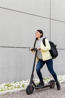 電動スクーターを持つ若い女性