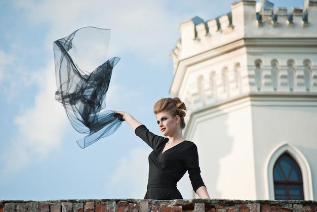 古典的なテラスで空飛ぶ生地と背景に城と曇り空のエレガントなドレスと若い女性