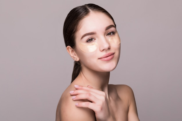 Young woman with an eye patches touching temples isolated on gray wall. cosmetics, skin stress concept