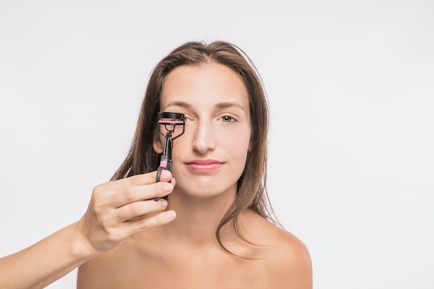 Young woman with eyelash curler on white background