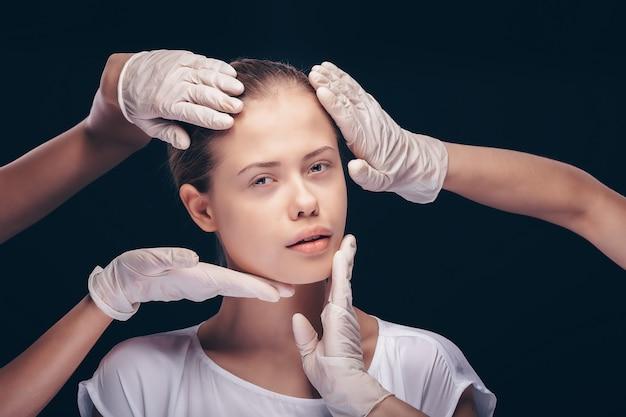 Молодая женщина с закрытыми глазами проходит медицинский осмотр кожи лица пластическими врачами