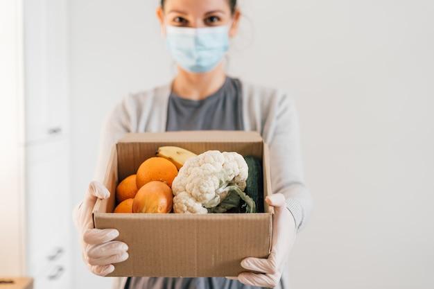 Молодая женщина с маска для лица и перчатки. доставка свежих продуктов на дом. ковид-19 карантинный шоппинг