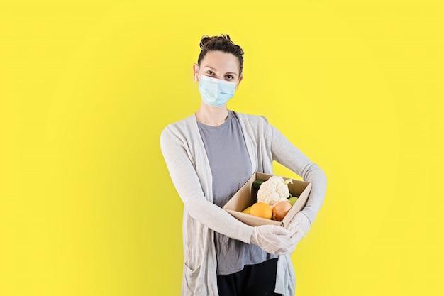 フェイスマスクと手袋を持つ若い女性。新鮮な製品を自宅に配達します。