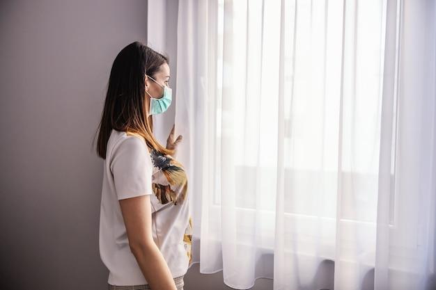 Молодая женщина с маской и перчатками, глядя в окно. чувство одиночества во время изоляции. карантинная меланхолия. оставайся дома.