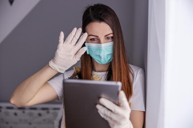 フェイスマスクと手袋のタブレットで入力を持つ若い女性。孤立しているときに孤独を感じる。憂鬱な検疫。家にいる。