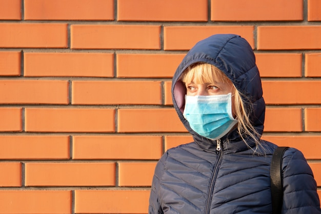 Young woman with face mask on the brick wall. novel chinese coronavirus concept of self-protection