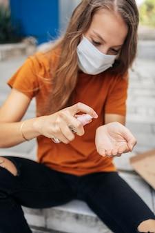 Giovane donna con maschera facciale disinfettando le sue mani