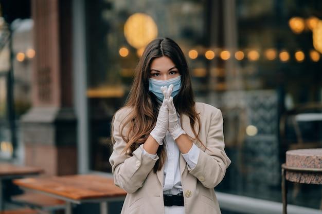 通りでフェイスマスクを持つ若い女性