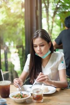 Молодая женщина с маской имеет еду в ресторане, новую нормальную концепцию.