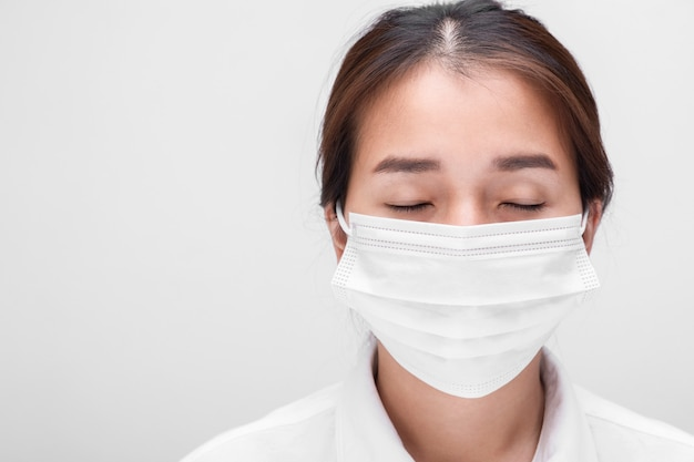 Young woman with face mask isolated on white background to prevent coronavirus & pm 2.5 air pollution, woman demonstrate how to wear virus protective face mask.