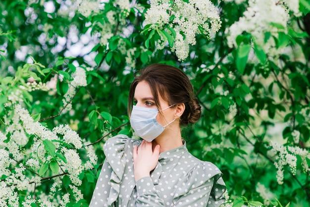 Молодая женщина с лицевой маской на открытом воздухе в цветущем саду. концепция вируса короны.