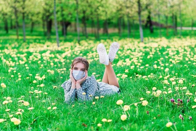 花の庭で屋外のフェイスマスクを持つ若い女性。コロナウイルスの概念。