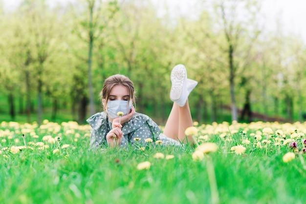 꽃 정원에서 야외에서 얼굴 마스크와 젊은 여자. 코로나 바이러스 개념.
