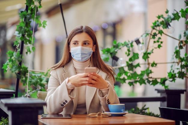 얼굴 마스크가 카페에 앉아 커피 브레이크를 마시고 스마트 폰을 사용하여 은행 계좌를 확인하는 젊은 여성