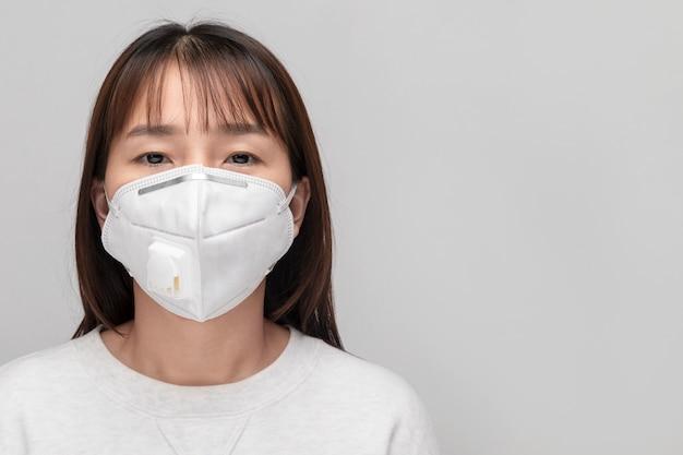 フェイスマスクを持つ若い女