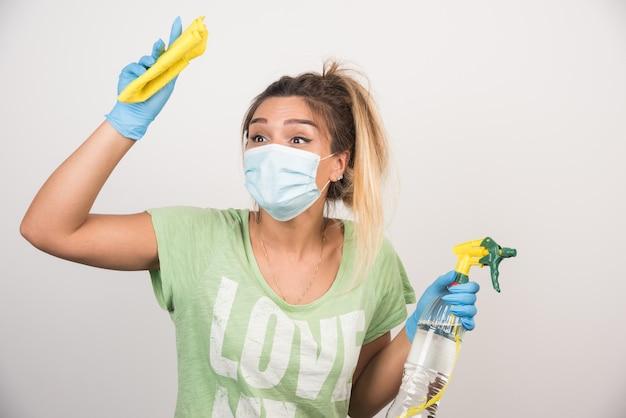 안면 마스크와 흰 벽에 물건을 청소 용품 젊은 여자.