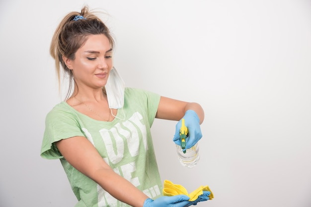 Young woman with facemask and supplies cleaning stuff.