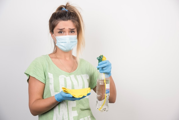 Young woman with facemask and supplies looking tired.