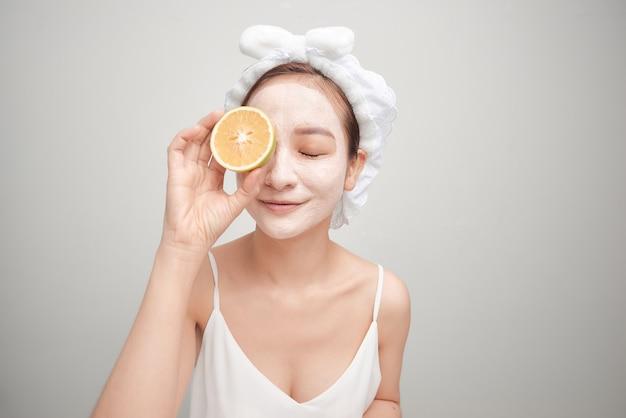 目を覆うオレンジ色の果物のスライスを保持している顔の粘土マスクを持つ若い女性