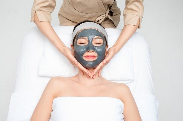 Young woman with facial mask in beauty salon