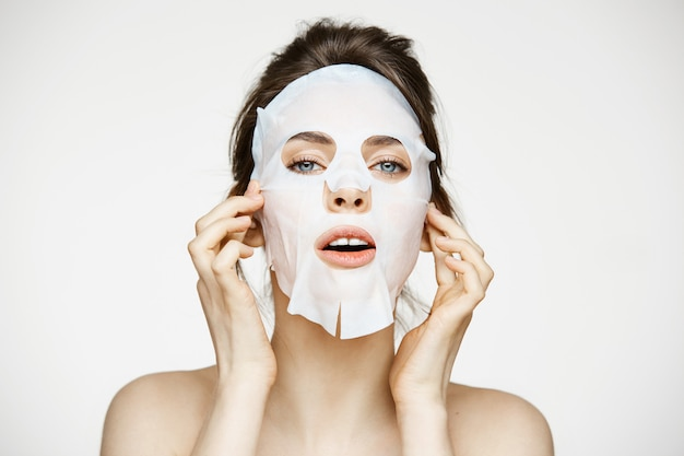 顔のマスクを持つ若い女性。美容スパと美容。
