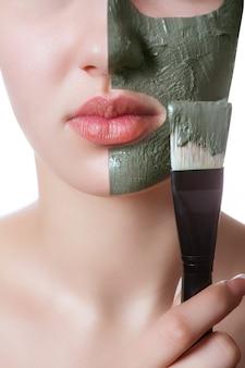ビューティースパでフェイシャルマスクを持つ若い女性。
