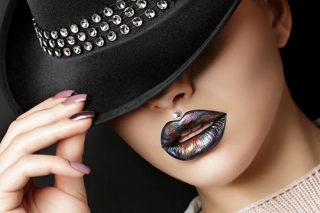ファッションの若い女性は、黒い帽子の下に目を隠してメイクアップします。ファッションの美しさの肖像画。モダンメイク。カラフルなメタリックの色合いの暗い唇。