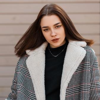 Молодая женщина в модном наряде на улице