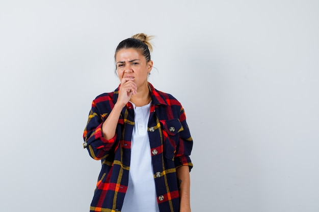 Young woman with finger in mouth in checkered shirt and looking puzzled , front view.