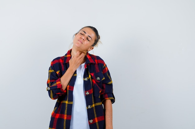 Young woman with fingers on neck in checkered shirt and looking painful , front view.