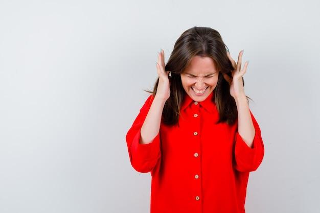 赤いブラウスの寺院に指を持ち、痛みを伴う、正面図を探している若い女性。