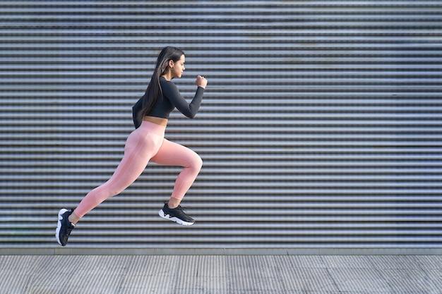 점프 하 고 실행 맞는 몸을 가진 젊은 여자. 운동복 운동하는 여성 모델