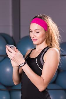 Молодая женщина с фитнес-трекер и смартфон в тренажерном зале