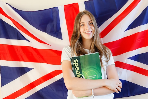 Young woman with flags of english speaking countries. english female student with the british flag at the background. english, learn, studying.