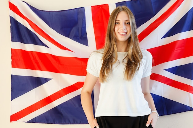 영어권 국가의 깃발을 가진 젊은 여자. 배경에서 영국 국기와 함께 영어 여성 학생. 영어, 배우기, 공부하기.