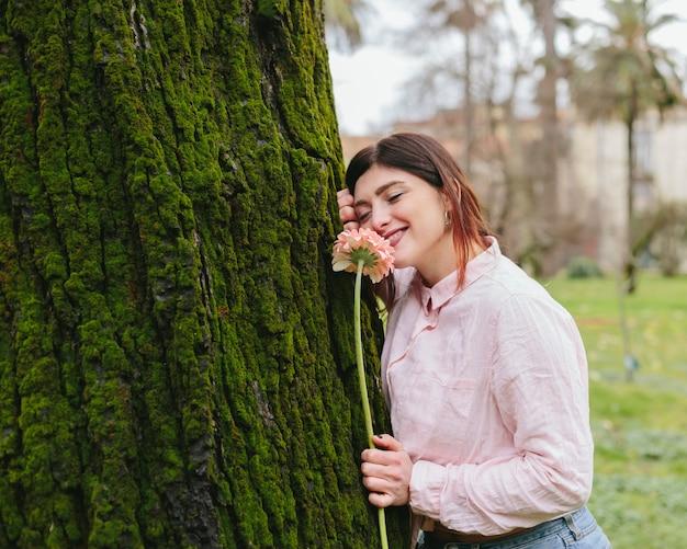 Giovane donna con il fiore che si appoggia sull'albero