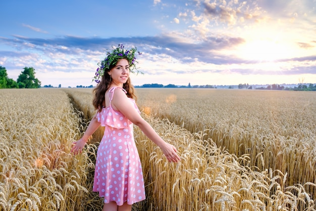 花の花輪を持つ若い女性が振り向いて笑顔