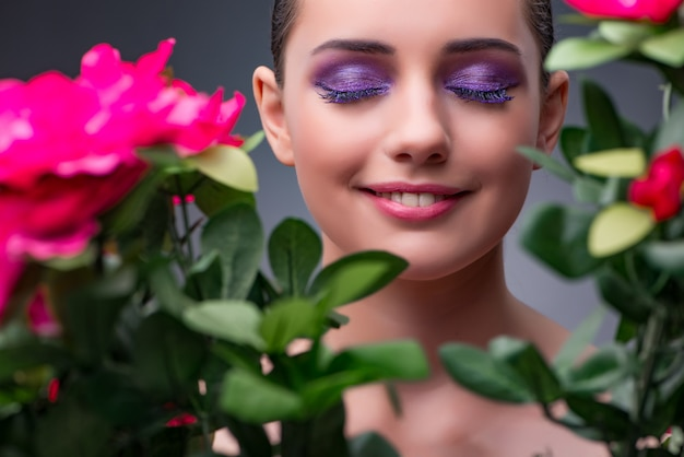 Young woman with flowers in beauty concept